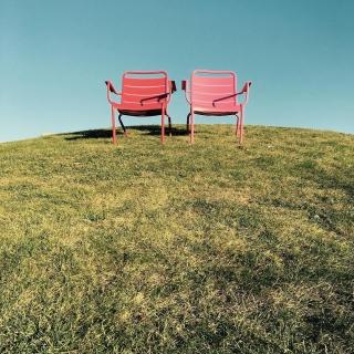 Die zwei roten Stühle auf dem  grünen Hügel.